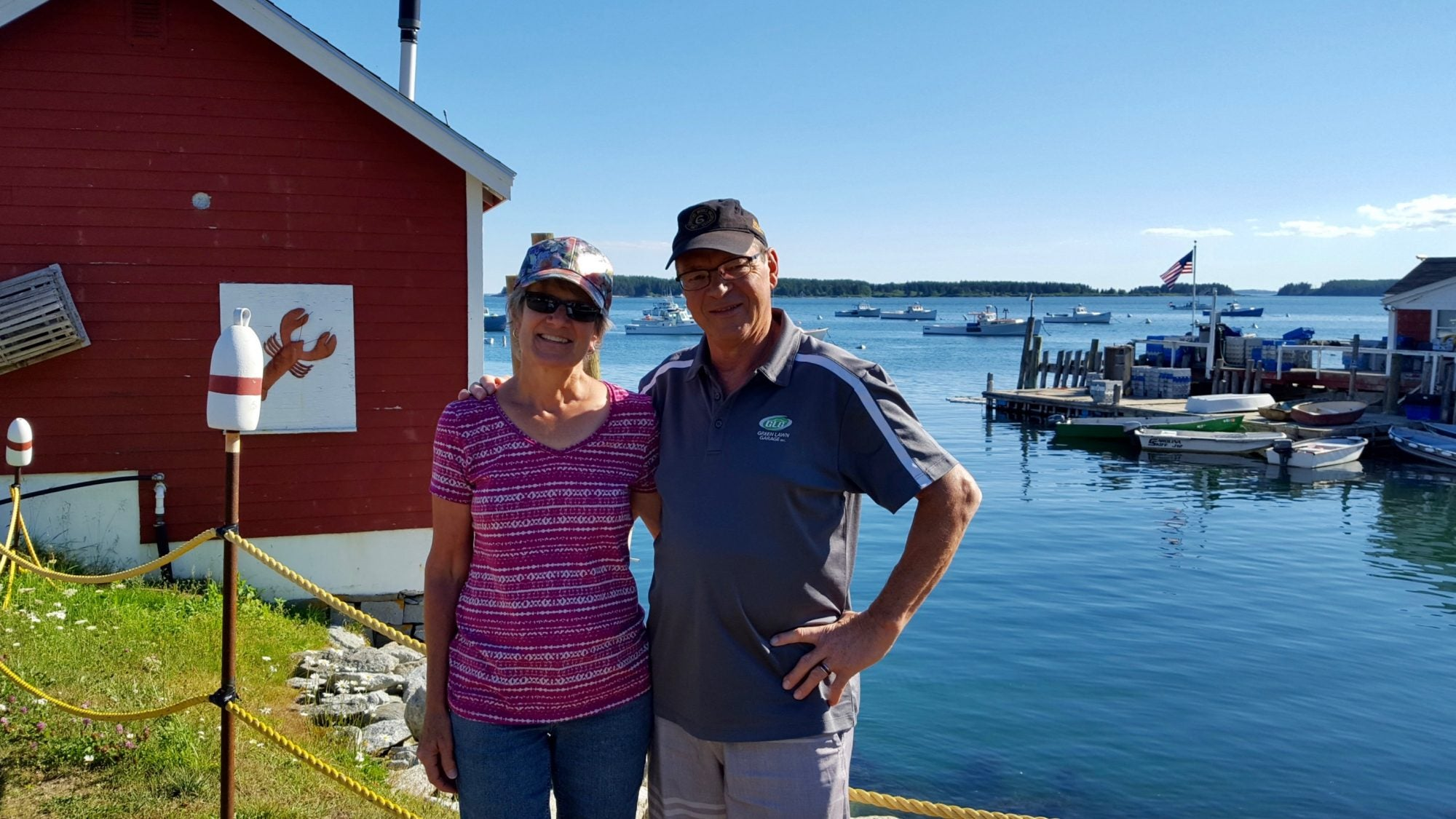 Image of older couple standing next to a small harbor in Maine