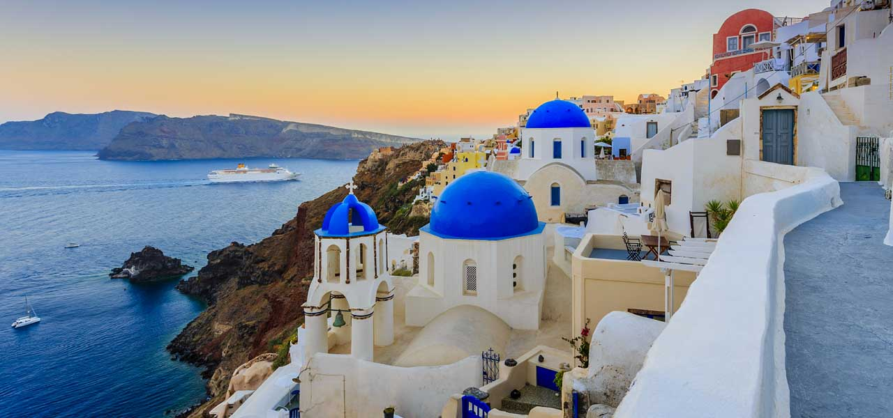 Image of an iconic Greek island hillside town with cruise ship passing in the background