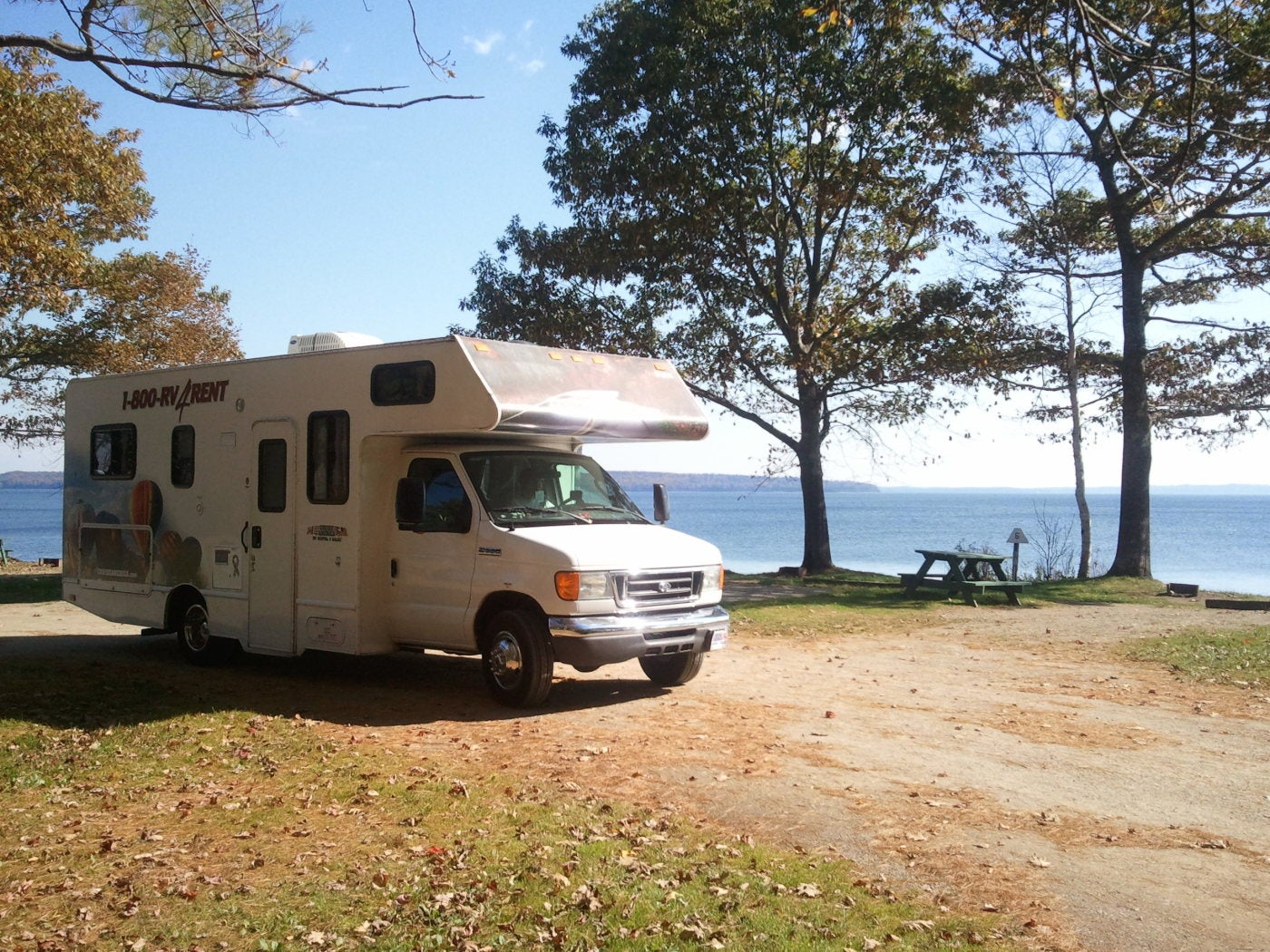 Image of recreational vehicle next to lake in late summer