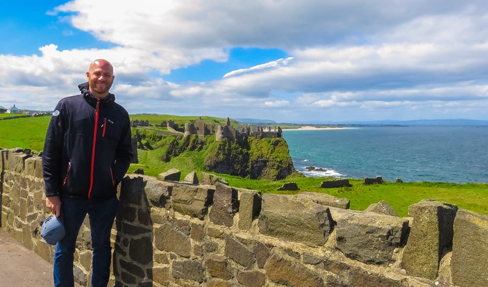 On a sunny day I'm standing in front of a low brick wall overlooking the blue Northern Irish sea and ruins of a gray Medieval castle that was part of the Game of Thrones television show that sits on lush green land