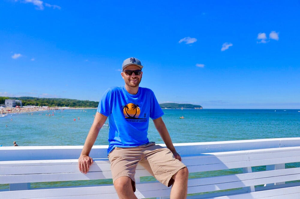 I'm sitting on a bench on the boardwalk in Sopot, Poland, in the summer. There's beautiful shimmering blue water. Gosh, I look handsome.