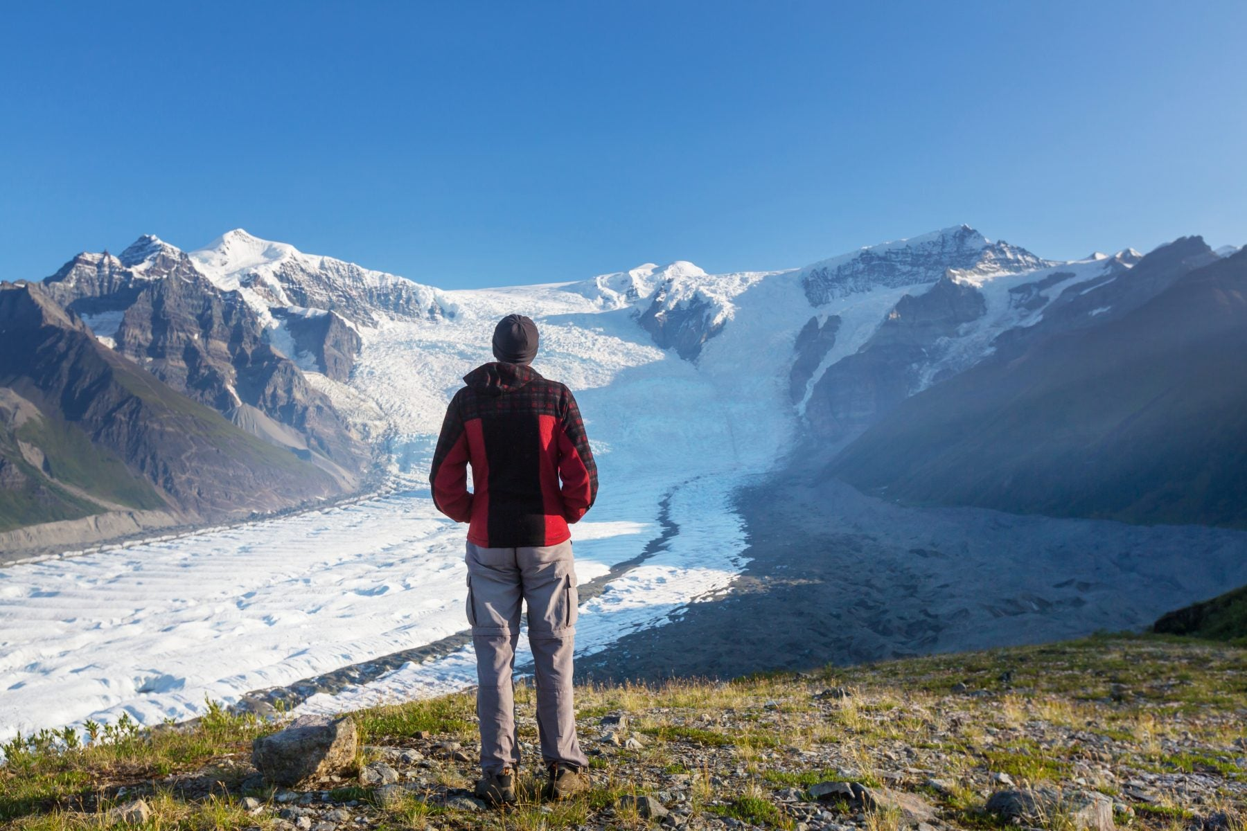 Man standing and looking out over glaciers