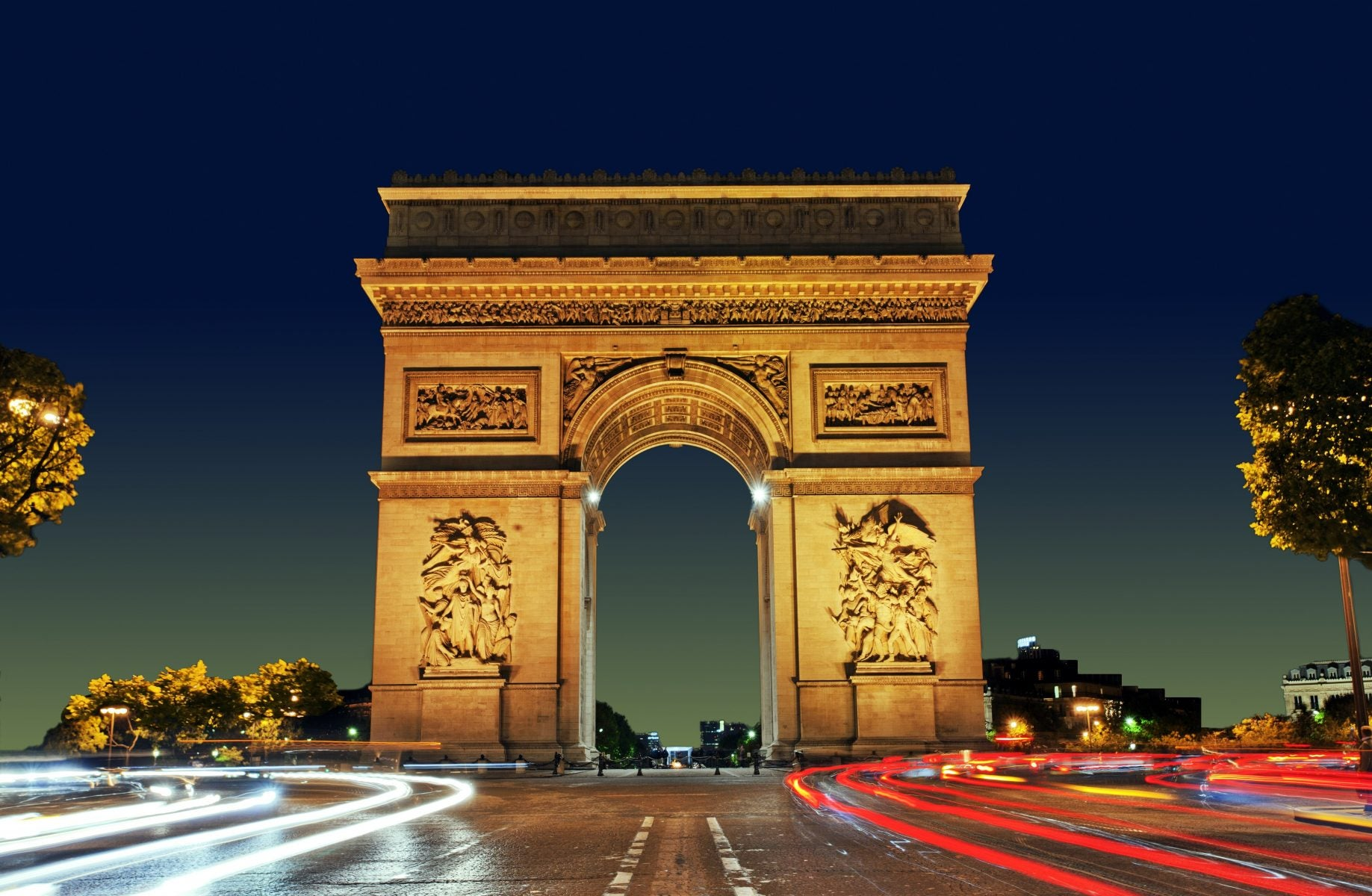 Arc de Triomphe with passing cars at night